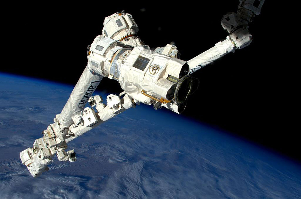 Astronauts give a 'hand' to robotic arm on spacewalk outside station